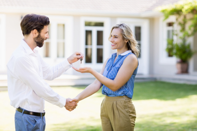 real estate agent shaking hands while giving keys to woman